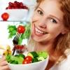 Eine lächelnde Frau mit Obst und Gemüse für eine gesunde Ernährung