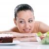 Eine Frau ist auf einen Tisch gelehnt, davor ein Stück Torte und Salat