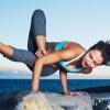 Eine Frau beim Yoga auf einem Stein, im Hintergrund Meer und Berge