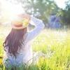 Frau sitzt im Gras und genießt die Frühlingssonne