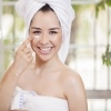 Eine Frau gibt Kosmetik ohne Konservierungsstoffe auf ihre Wange