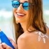 Eine Frau hat Sonnencreme in der Hand für die Gesichtspflege mit UV Schutz