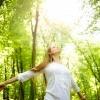 Eine Frau steht im Wald mit guter Laune im Frühling