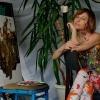 Innenaufnahme einer Künstlerin, die in einem Studio auf einer Leinwand malt.