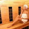 Eine Frau sitzt in einer Infrarotkabine die Wirkung auf die Haut hat