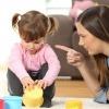Eine Mutter ermahnt ihr spielendes Kleinkind mit erhobenem Zeigefinger.