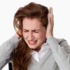 Eine Frau hält sich wegen Kopfschmerzen oder Tinnitus die Ohren zu