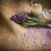 Lavendelblüte liegt vor einer Kerze