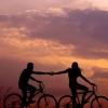 Ein Pärchen fährt gemeinsam mit dem Fahrrad einen Berg hoch, während hinter ihnen die Sonne untergeht.