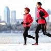 Ein Mann und eine Frau joggen vor einer winterlichen Stadt