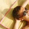 Ein Mann liegt in der Sonne am Strand