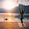 Eine Frau meditiert neben einem See in der Natur