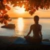 Eine Frau meditiert vor einem Fluss