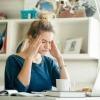 Eine Frau greift müde auf ihren Kopf