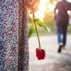 Eine Frau hält eine Rose in der am Körper anliegenden Hand, während ihr Partner sich von ihr weggeht.