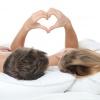 Ein Paar liegt im Bett und formt ein Herz mit den Händen