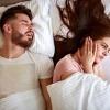 Frau im Bett hält sich die Ohren zu, weil der Partner schnarcht