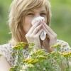Pollenallergie Symptome zeigt eine Frau, die in einer Wiese steht