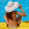 Eine Frau sitzt am Pool uns wirkt, als hätte sie Selbstbräuner verwendet