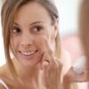 Eine brünette Frau blickt in den Spiegel und trägt sich Creme in ihr Gesicht auf.