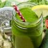 Grüne Smoothies stehen zwischen Erdbeeren und grünem Gemüse