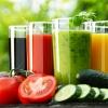 Gläser mit Smoothies stehen von Gemüse umlagert