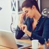 Eine Frau hält eine Brille und reibt im Stress Augen und Nase