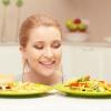 Auf dem Foto sind zwei Teller und eine blonde Frau abgebildet. Auf dem einen Teller befindet sich gesundes, auf dem anderen ungesundes Essen.