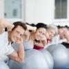 Männer und Frauen trainieren mit einem Gymnastikball
