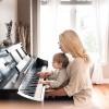 Eine Mutter sitzt mit einem Kind beim Klavier als typengerechte Erziehung