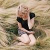 Eine Frau sitzt in wildem trockenen Gras