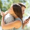 Ein Mann und eine Frau umarmen sich mit Blick auf das Handy