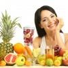 Eine Frau sitzt vor Obst und will Vitamine für Kosmetik