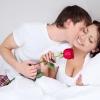 Ein Mann küsst als Vorspiel den Hals einer Frau und hält eine Rose