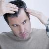 Ein Mann schaut in den Spiegel und fragt sich was tun gegen graue Haare?