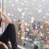 Junge Frau sitzt im Winter verstimmt am Fensterbrett