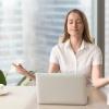 gestresste Frau sitzt vor ihrem Laptop und greift sich auf den Kopf