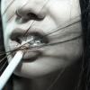 Einer Frau hängt eine Zigarette aus dem Mund
