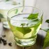 Grüne Blätter liegen in einer Tasse mit grünem Tee