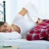 Eine Frau mit Bauchschmerzen liegt im Bett
