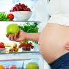 Eine schwangere Frau steht vor dem Kühlschrank