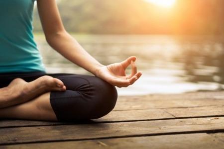Eine Frau ist in Balance und meditiert vor einem See